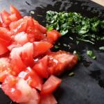 Eine frische, kleingeschnittene Tomate und etwas kleingehackter Basilikum