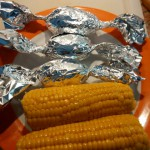 Vorbereitete Folienkartoffeln und Maiskolben