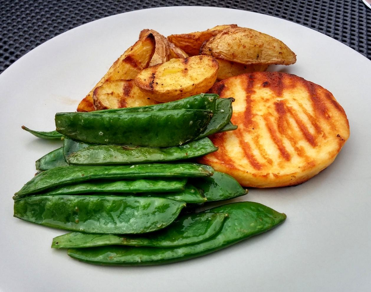 Kaiserschoten mit Kartoffelspaten und Grillkäse auf Teller angerichtet