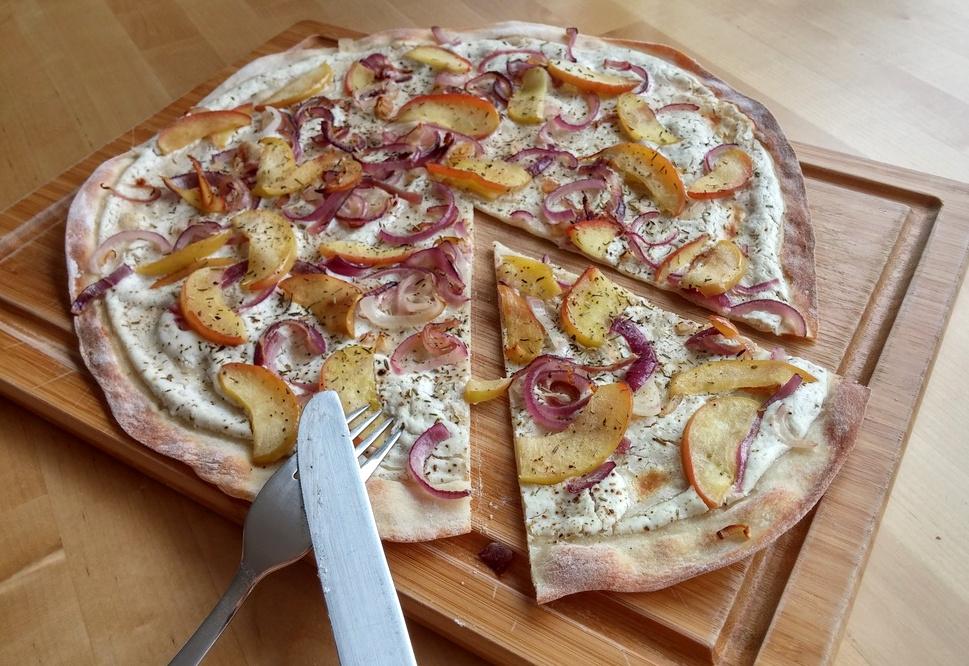 Apfel-Ziegenkäse-Flammkuchen mit angeschnittenem Stück
