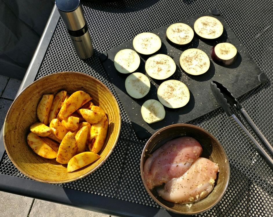 Auberginen, Kartoffeln und Hähnchen stehen zum Grillen bereit