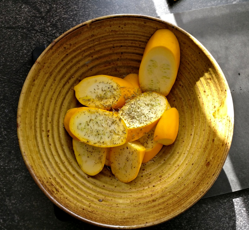 Gelbe Zucchini wird mit Olivenöl und Kräutern gewürzt