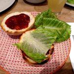 Burger-Buns mit BBQ-Sauce bestreichen und Salat auf eine Hälfte legen