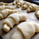 Croissants liegen zum Bestreichen mit Ei bereit