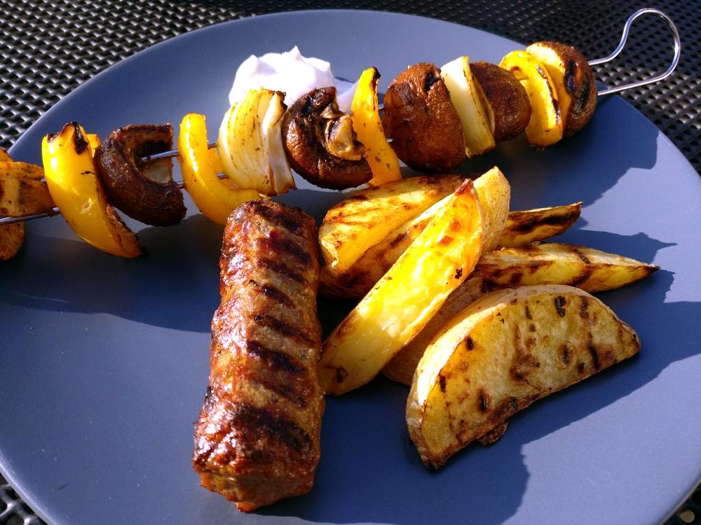Cevapcici mit Kartoffelspalten und Thymian-Gemüsespießen