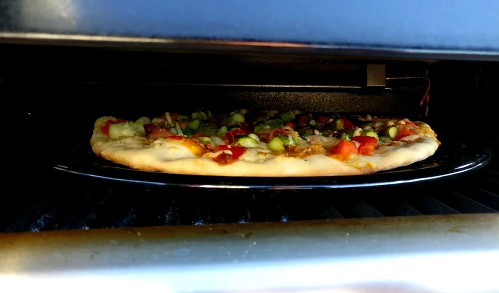 Ein Blick unter die Haube auf die Pizza mit grünem Spargel