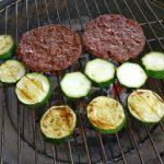 Die Hamburger Patties und Zucchini wird auf dem Holzkohlengrill zubereitet