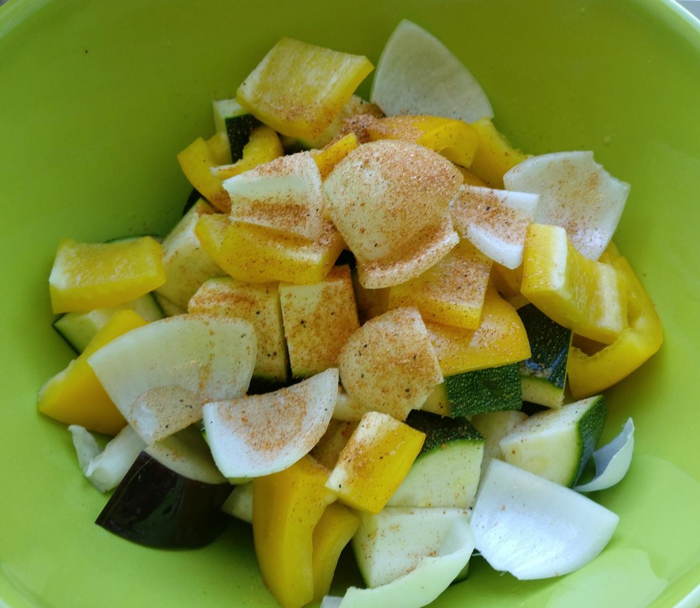Paprika, Zwiebeln, Zucchini und Aubergine werden mit Salz und Öl mariniert