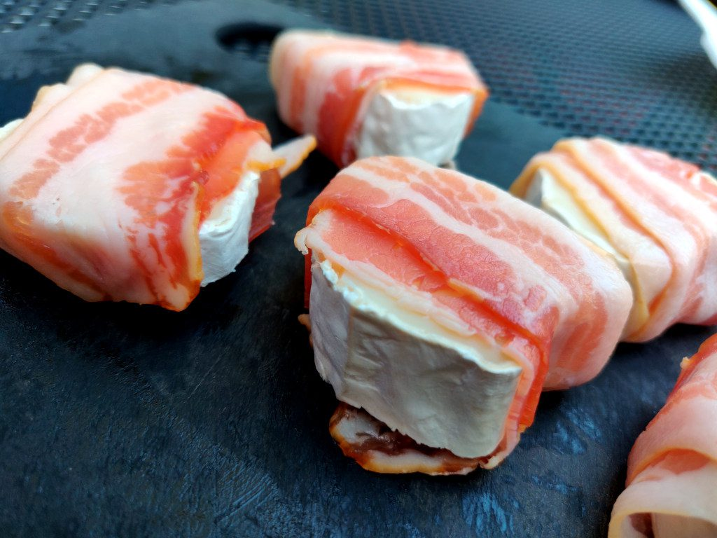 Die Ziegenkäsescheiben werden jeweils mit einer Scheibe Bacon umwickelt