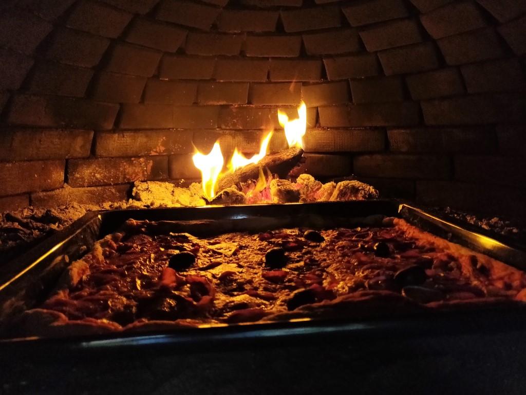 Die Pizza backt im Steinofen