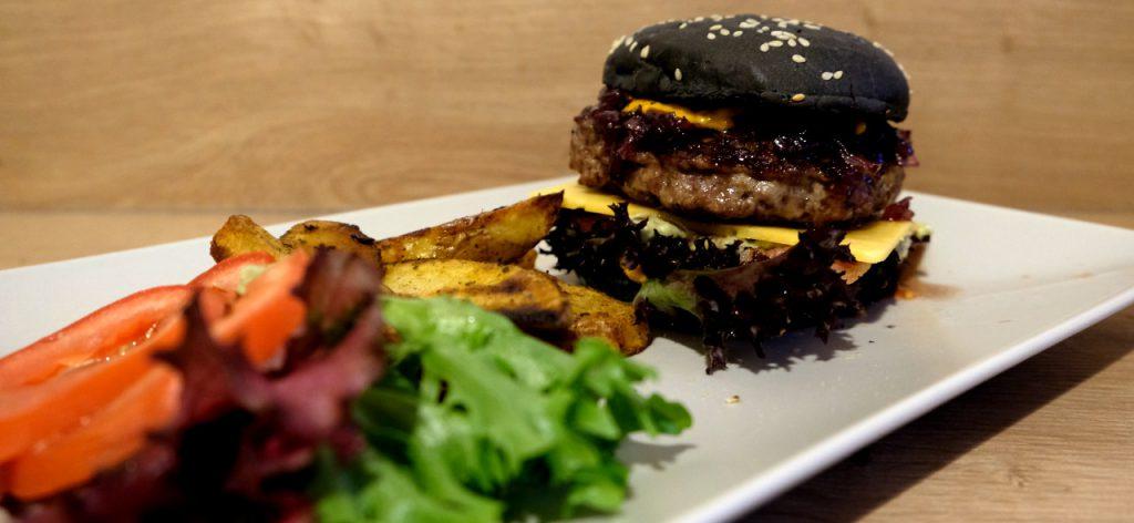Black Burger mit Zwiebel-Chutney, Wedges und Salat