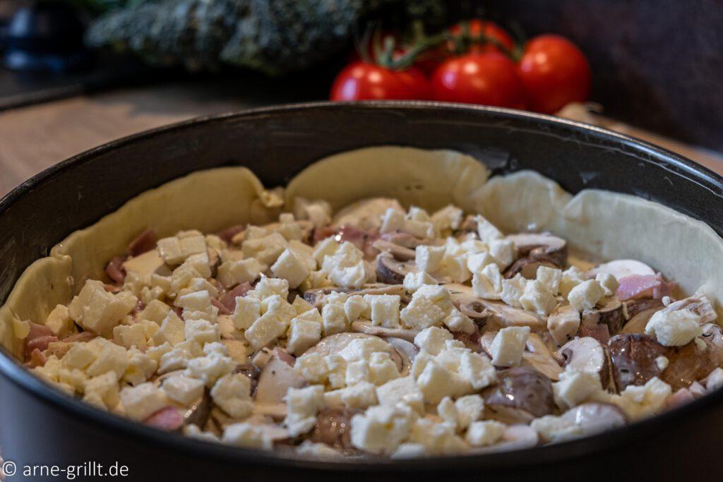 Nun kann die Quiche mit frischen Champignons und Schinken auf den Grill